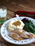 turkey breast slices with gravy with mashed potatoes, green beans and cranberry sauce on side.