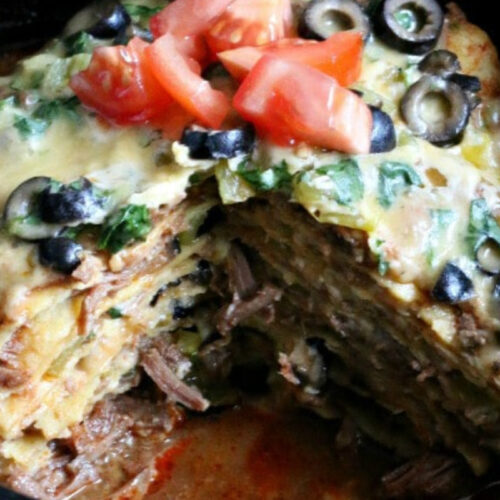 Beef and corn tortillas stacked together with cheese, tomato and olives on top.