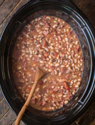 black eyed peas cooked in the slow cooker with a wooden spoon in them.