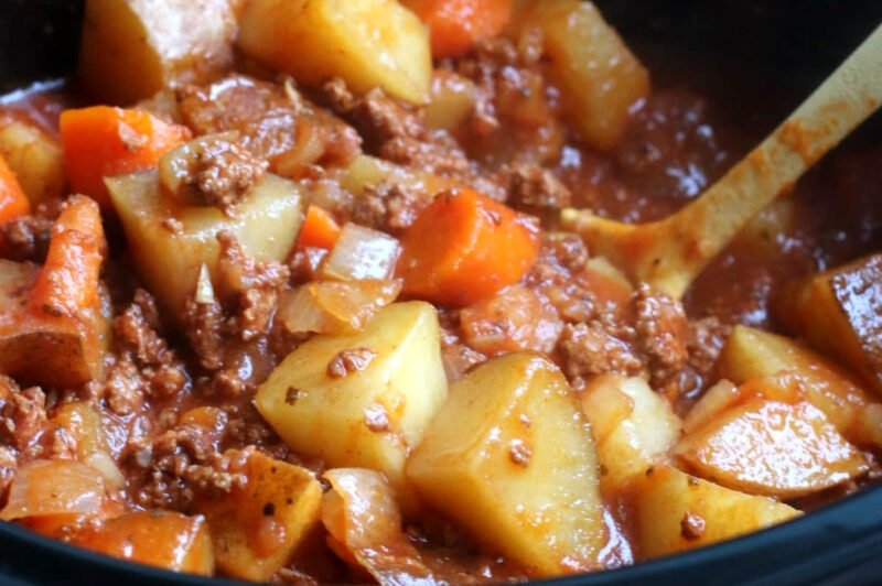 close up of stew with potatoes, carrots and ground beef. Yellow spoon in it.