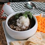 bowl of black bean soup with rice on top.