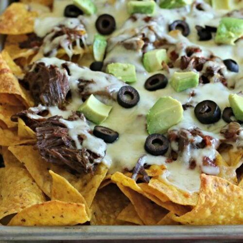shredded beef nachos on a sheet pan