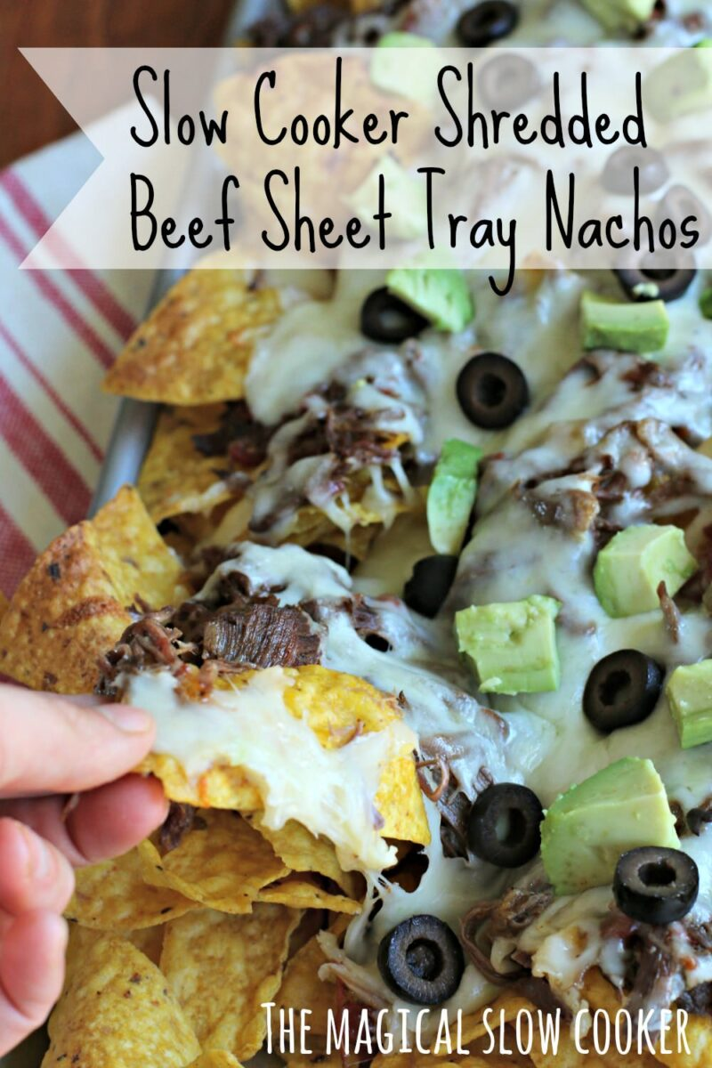 Nachos on sheet try with hand grabbing a chip.