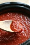 wooden spoon dipping out marinara sauce