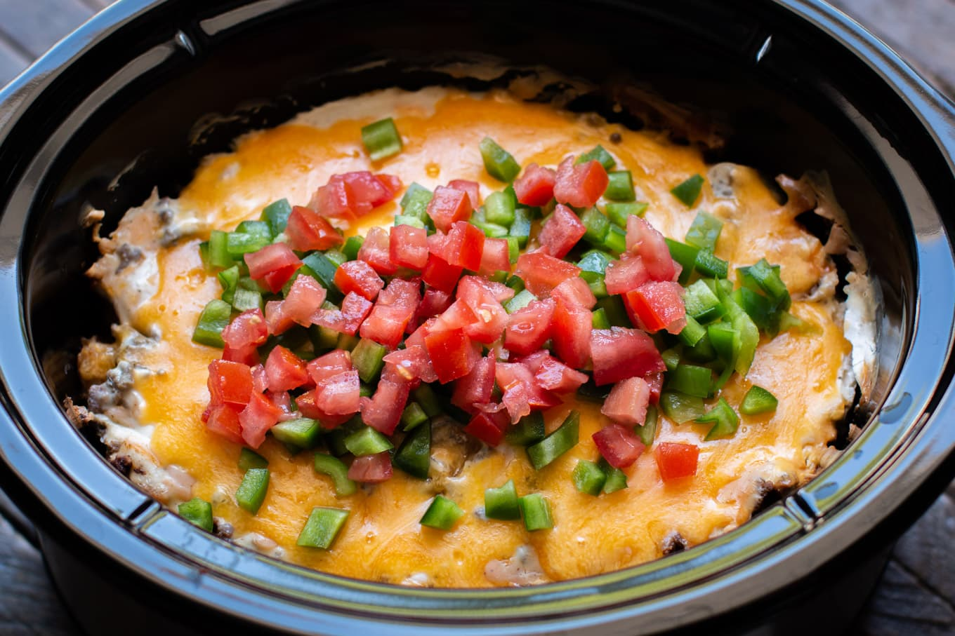 John Wayne casserole in the slow cooker with bell pepper and tomatoes on top.