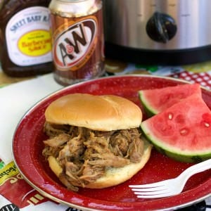 pulled pork sandwich on red plate with watermelon on the side.