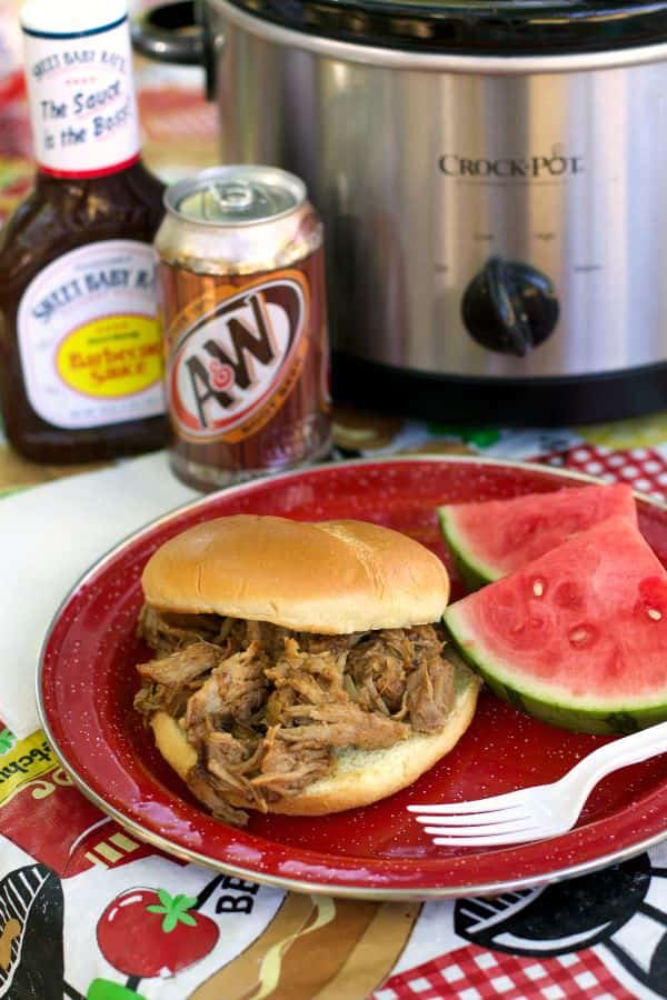 rootbeer pulled pork sandwich on red plate with watermelon on side