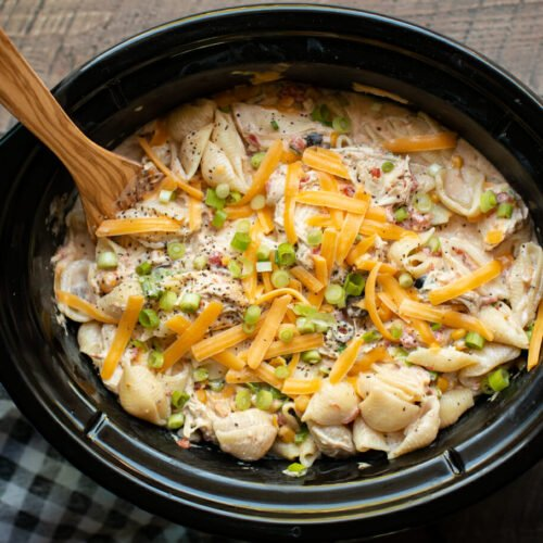 shell pasta dish with chicken, cheese and green onion on top, in slow cooker.