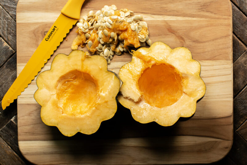 cut open acorn squash with seeds gutted out on cutting board