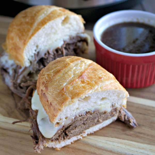 French dip sandwich on cutting board with aujus next to it.