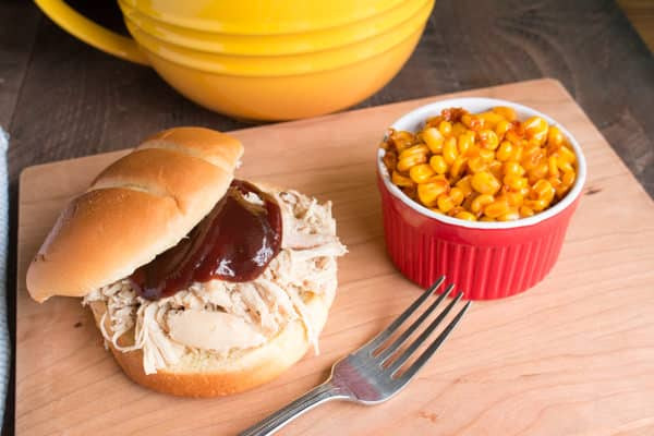 shredded chicken sandwich with corn on the side.
