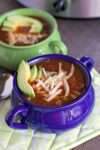 2 bolwls of vegetarian chili with cheese and avocado on top.
