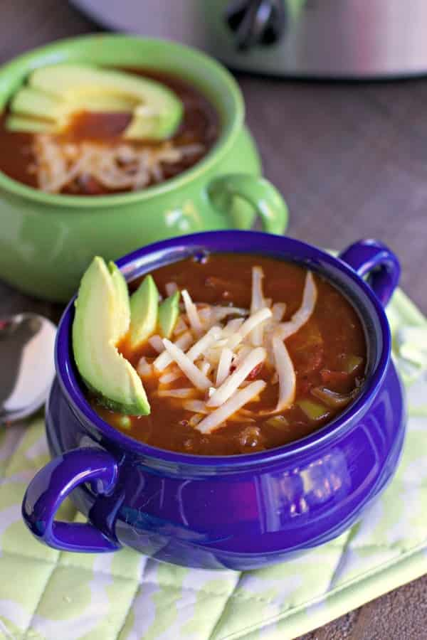 2 bowls of chili with avocado on top and white cheese