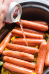 beer being poured over brats in slow cooker.