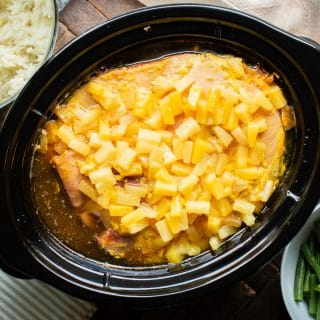 ham in slow cooker, cooked with pineapple tidbits on top.