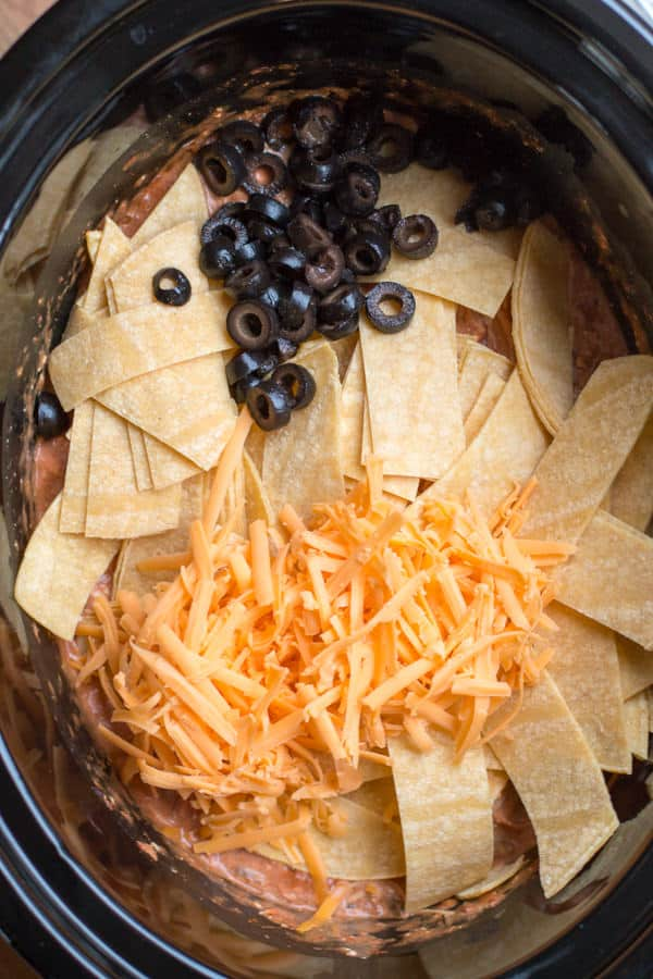 corn tortilla strips, olives, and cheese on top of shredded chicken in slow cooker.
