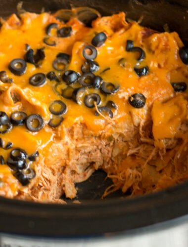 chicken enchilada casserole in slow cooker with scoop missing.