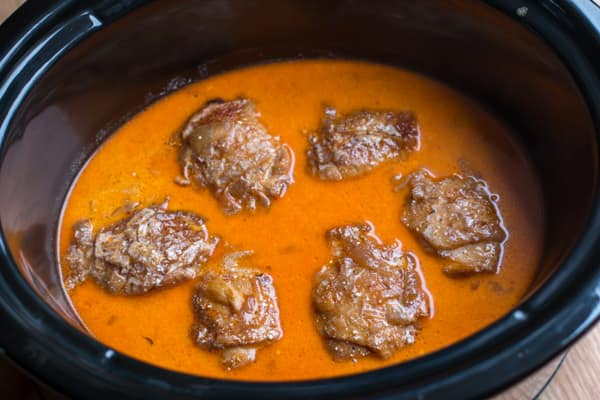 Six skin-on chicken thighs in paprika sauce in slow cooker.