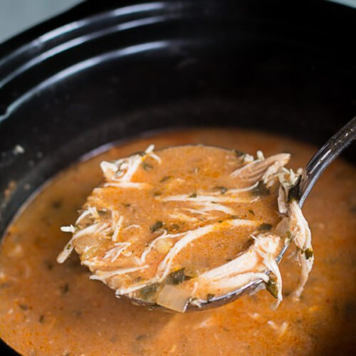 chicken enchilada soup in slow cooker with ladle scooping it out.