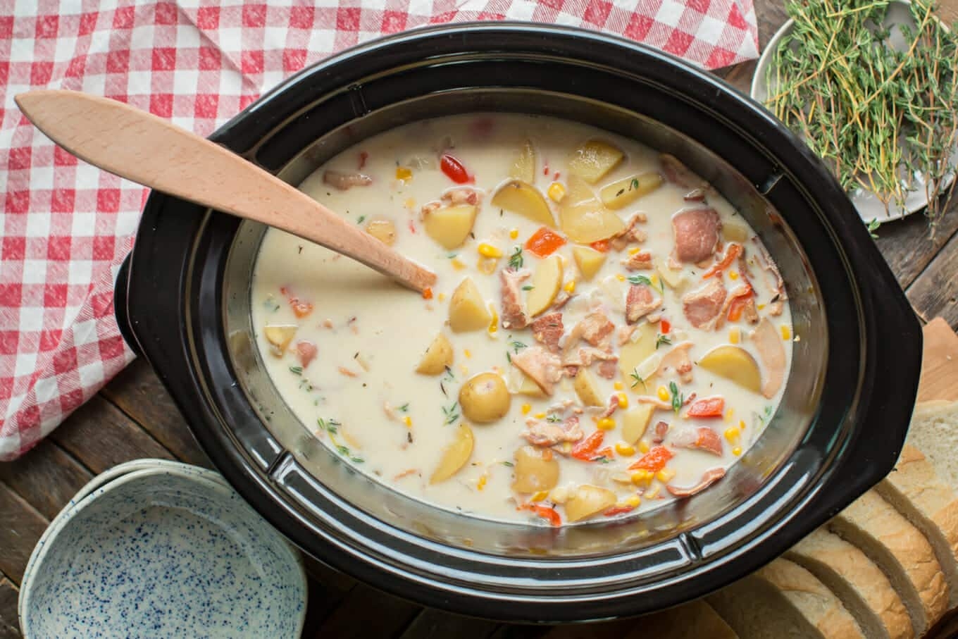 corn chowder in a slow cooker with wooden spoon in it.