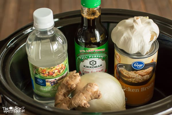 ingredients for chicken adobo in crockpot; vinegar, soy sauce, onion, chicken broth, garlic and ginger