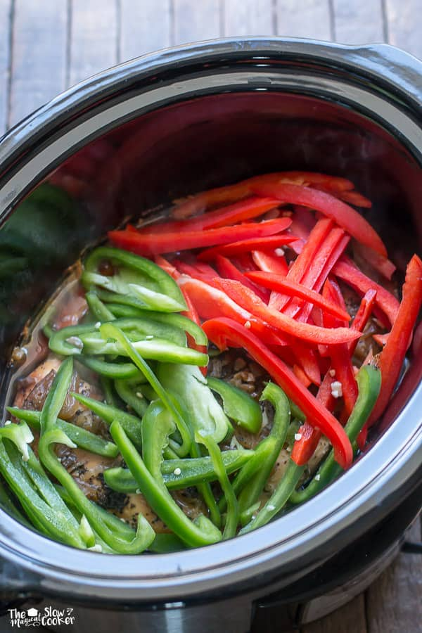 Cooked chicken in slow cooker with red and green bell peppers on top.