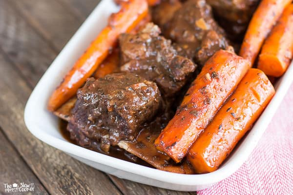 close up of short ribs and carrots in white platter