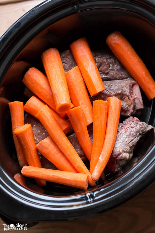Slow cooker filled with short ribs with carrots on top.