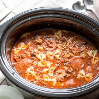 pizza soup in slow cooker with pepperoni and bowtie pasta in it.