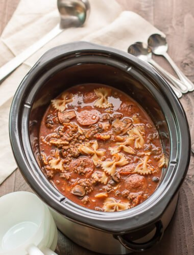 slow cooker with pizza soup in it, ladle and spoons on side