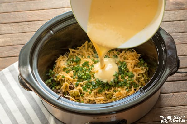 Whipped eggs being poured over sausage, cheese, chiles and green onions in slow cooker.