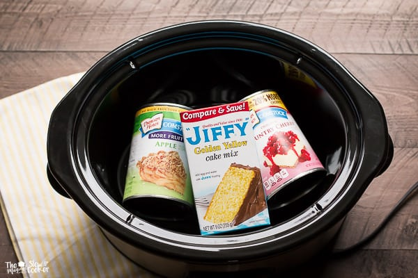 Cans of apple and cherry pie filling and box of jiffy yellow cake mix in slow cooker.