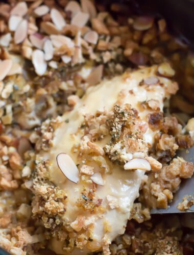 close up of chicken breast with stuffing and almonds on top.