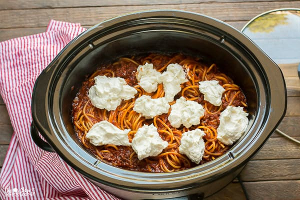 Spaghetti with meat sauce with dollops of cream cheese and ricotta on top.