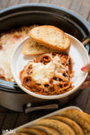plate with spaghetti and garlic bread on side, slow cooker in background