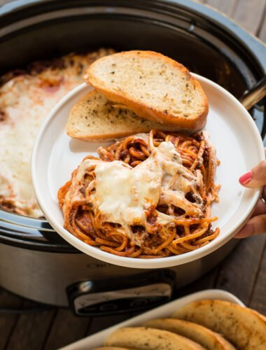 plate with baked spaghetti with cheese, garlic butter on the side.