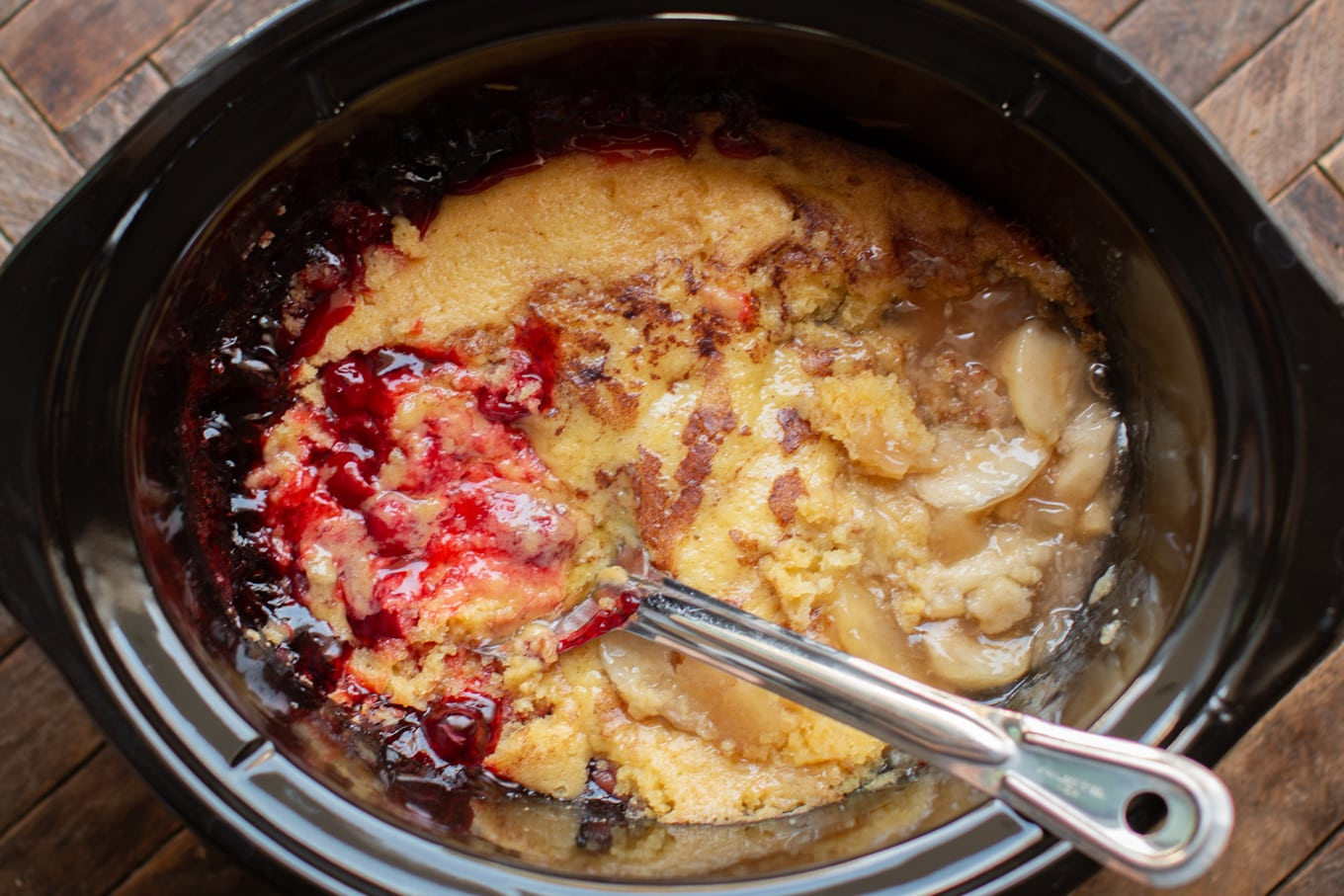 Spoon in cherry and apple cobbler in slow cooker.
