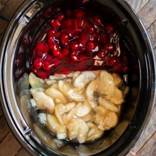 cherry pie filling on half of slow cooker and apple on the other half.