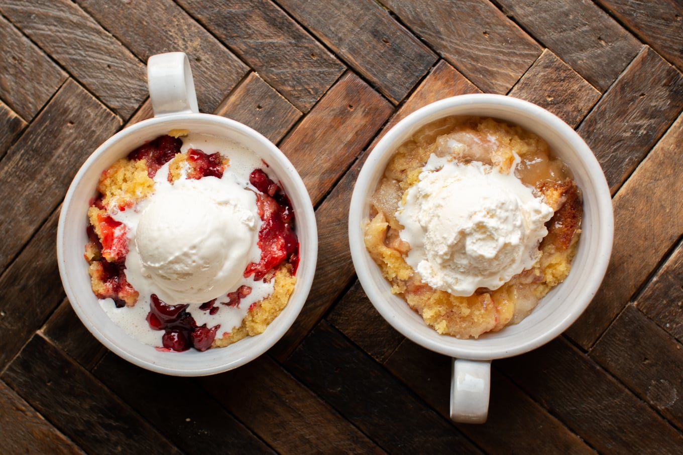 Bowl of cherry cobbler, bowl of apple cobbler both with ice cream on top.