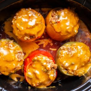 5 meatloaf stuffed peppers with cheese on top in slow cooker, in salsa