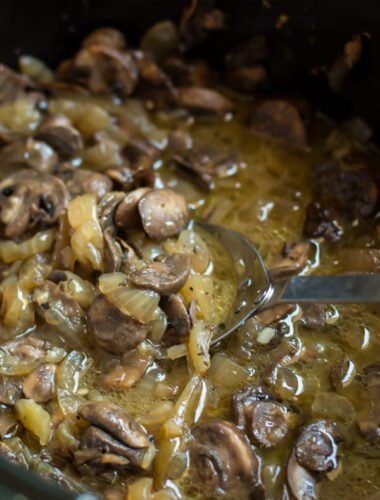 cooked mushrooms and onions in a buttery sauce in slow cooker