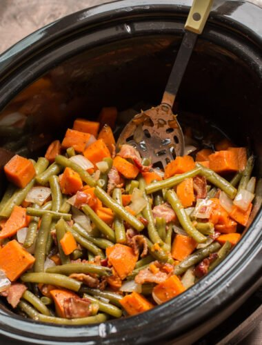 sweet potatoes and green beans in slow cooker with spoon in it.