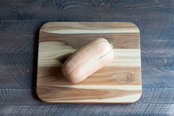 One whole butternut squash on a cutting board.