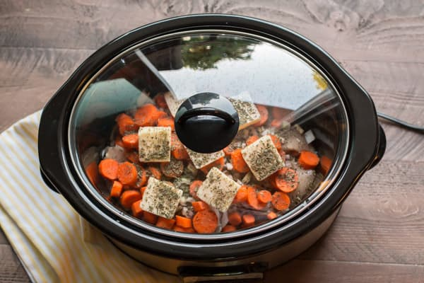 chicken, butter, carrots and seasonings in a slow cooker.