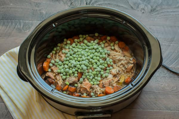 peas on top of shredded chicken in a slow cooker