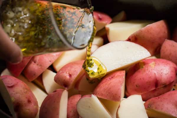 Pouring oil and herbs over red potatoes.