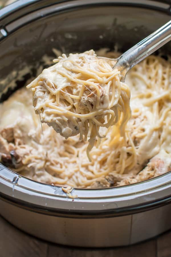 chicken tetrazzini on a ladle coming from a slow cooker.