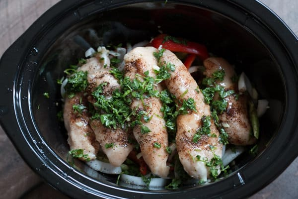 chicken thighs, onions, peppers and cilantro in a slow cooker.