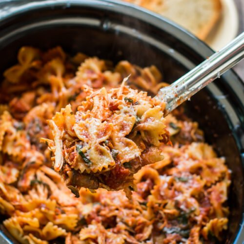 chicken bacon pasta on a ladle coming from a slow cooker.