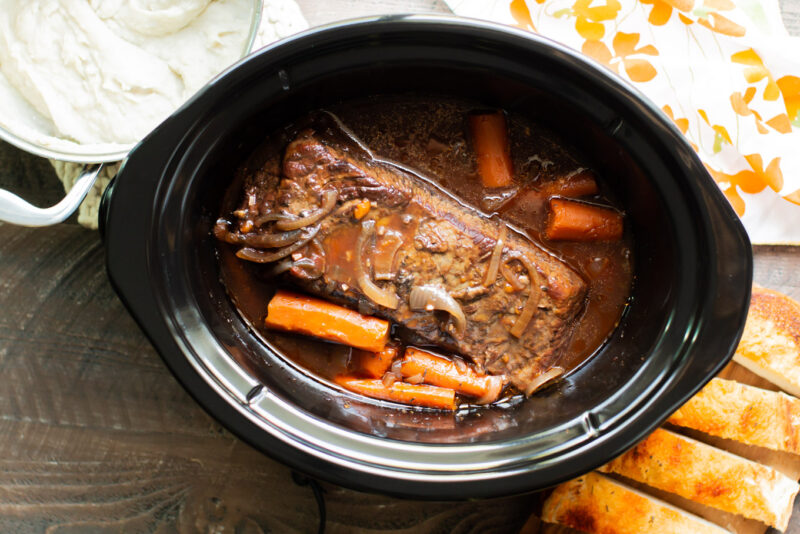 finished cooking brisket in the slow cooker with mashed potatoes and carrots on the side.
